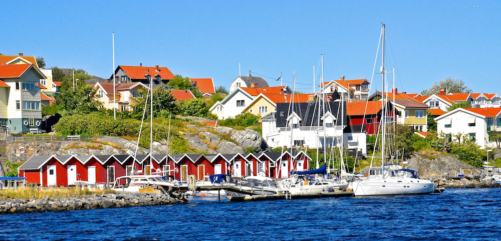 Sailing past Kalvholmen - fishing huts painted in the typical Swedish red, called Faluröd, with white trim | Cruising Attitude Sailing Blog - Discovery 55